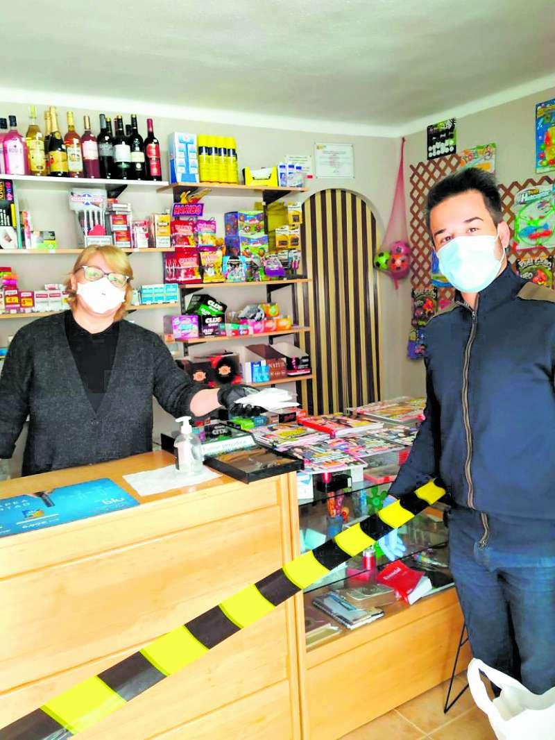 El alcalde proporciona mascarillas a una vecina que regenta uno de los comercios locales que permanecen abiertos. / EPDA
