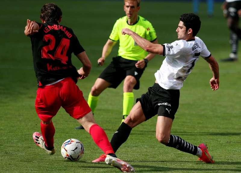 El delantero portugués del Valencia Gonçalo Guedes (d) lucha por el balón con el defensa galo Robin Le Normand, de la Real Sociedad.