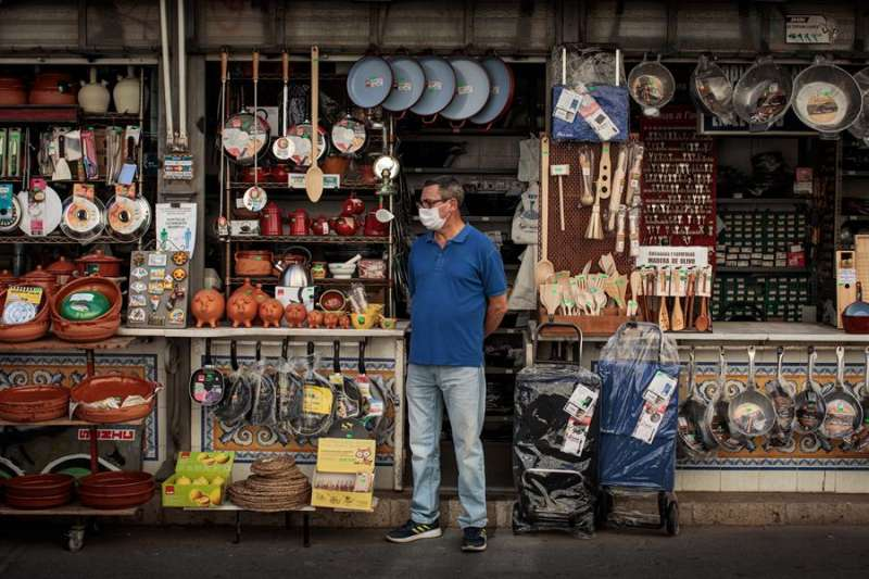 Imagen de archivo de un comerciante esperando a las puertas de su comercio que lleguen clientes. EFE