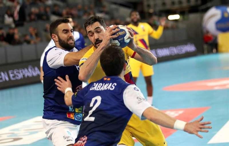 El jugador del FC Barcelona Raúl Entrerríos (c) lucha con el jugador de Balonmano Benidorm Álvaro Cabanas (d), durante la final de la Copa del Rey de balonmano. EFEArchivo