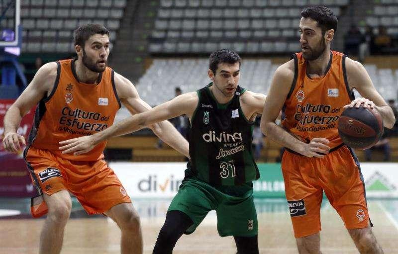 Joan Sastre (d) y Mike Tobey (i), del Valencia Basket Club, intentan avanzar ante la oposición de Dakota Mathias (c), del Divina Seguros Joventut. EFE/Archivo