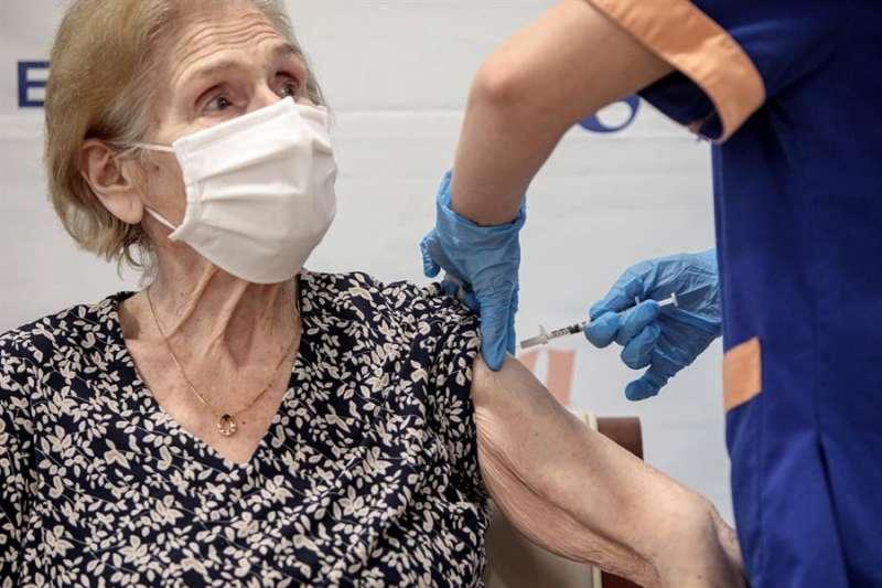 Imagen de archivo de un sanitario inyectando la vacuna para la covid-19 a una anciana en una residencia de Valencia. EFE