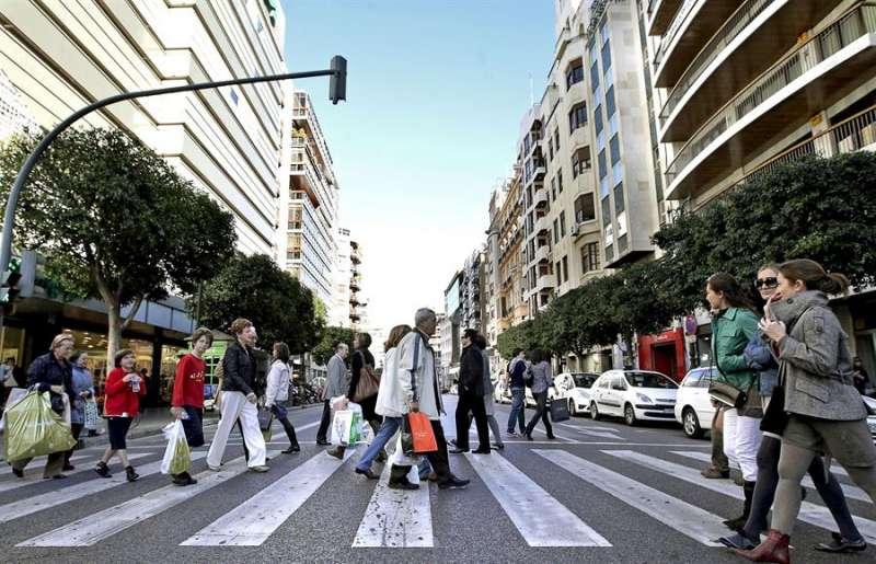 Numerosas personas cruzan la céntrica calle Colón, en Valencia. EFE/Manuel Bruque.
