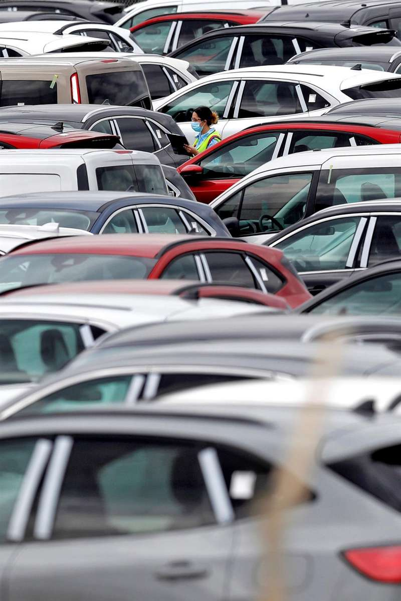 Una trabajadora de Ford camina entre automóviles aparcados en el exterior de la planta en Almussafes y listos para ser enviados a los concesionarios.