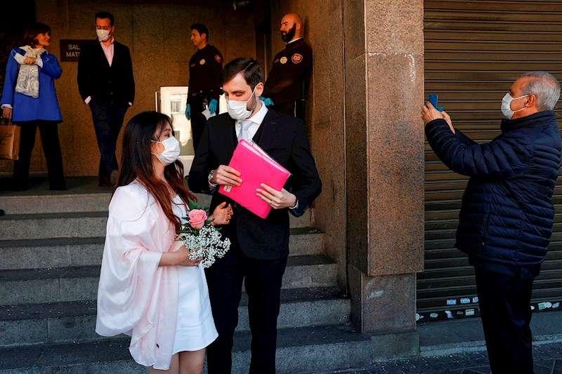Unos recién casados protegidos con mascarillas salen de una sede del Registro Civil, en una imagen del 13 de marzo. EFE