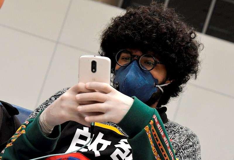 Un joven con mascarilla y guantes consulta su teléfono móvil. EFE/Archivo