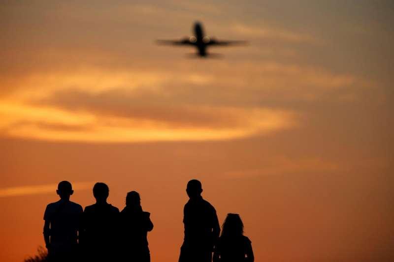 Varios turistas miran desde un alto, a los aviones tras despegar, en Alicante. EFE / Manuel Lorenzo/Archivo