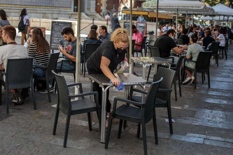 Una camarera limpia una mesa de una terraza.