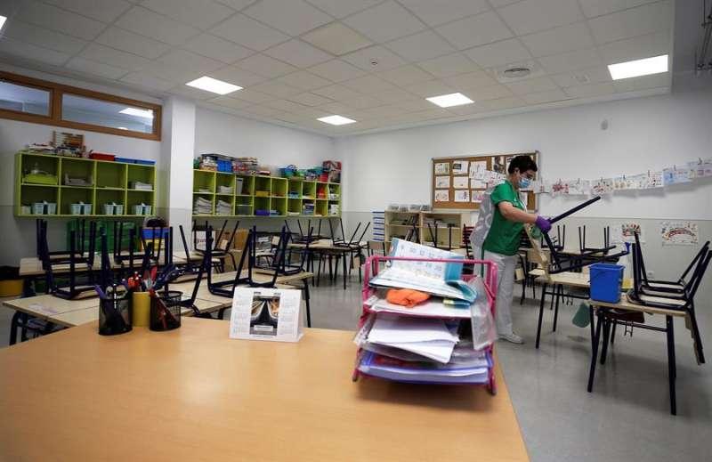 Una trabajadora del servicio de limpieza desinfecta las sillas y los pupitres de una clase de infantil del colegio CEIP 103 de Valencia. EFE