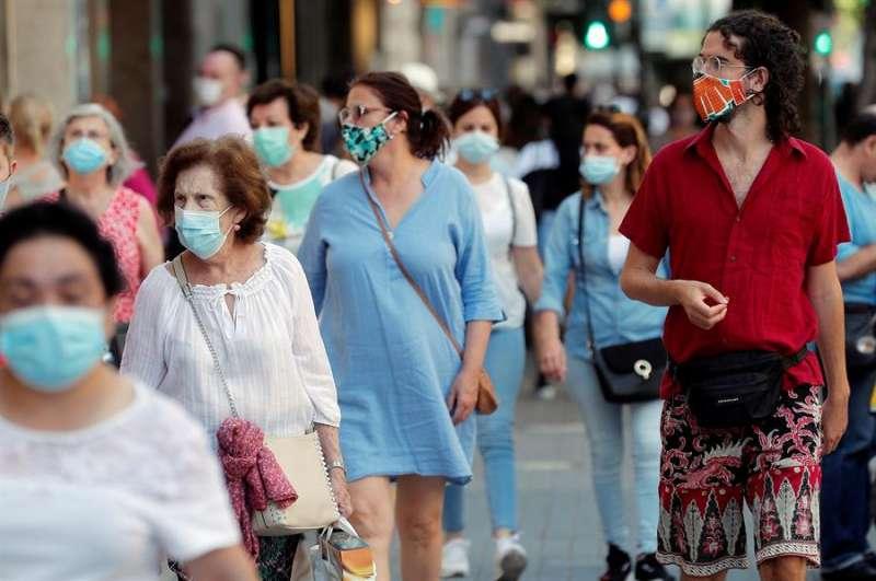 Varios transeúntes, todos ellos con mascarilla, pasean por una calle de València. EFE/Kai Försterling