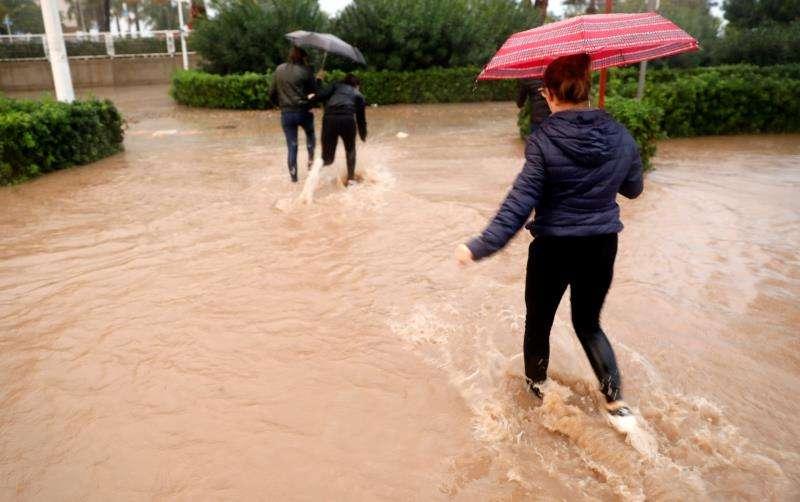 València (Comunitat Valnciana), 16/11/2018.-Varias personas cruzan una calle inundada durante la tarde de hoy en la que el temporal de lluvia torrencial ha azotado por tercera jornada consecutiva la provincia de Valencia. EFE/Kai Försterling