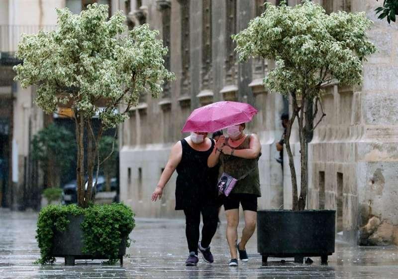 Dos personas caminan bajo la fina lluvia en Valencia. EFE/ Juan Carlos Cárdenas/Archivo