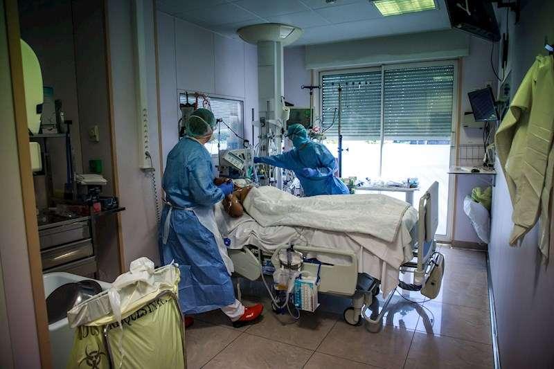 Médicos atendiendo a un paciente en una UCI. EFE
