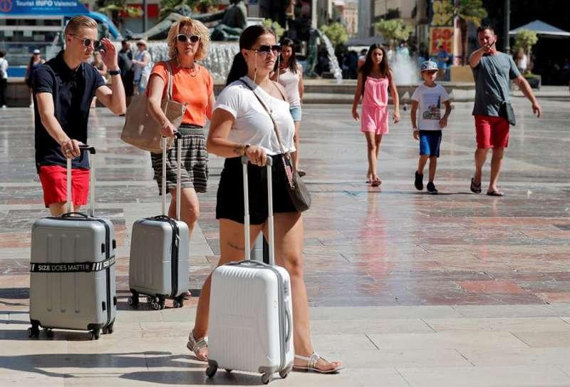 Tres turistas pasean con sus maletas por el centro de València. EFE/Kai Försterling/Archivo